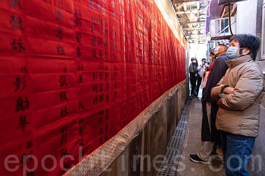 村民在「人緣榜」上查看自己和家人的姓名。(陳仲明/大紀元)