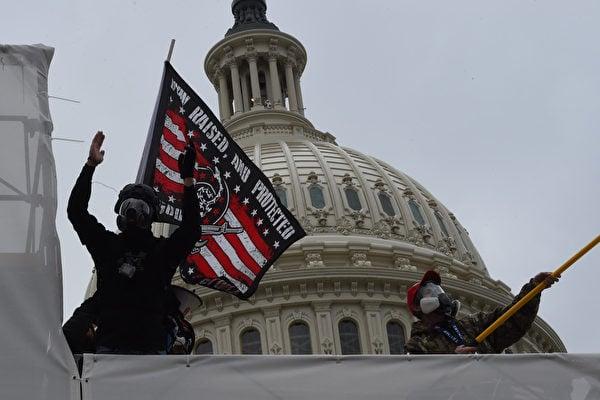圖為2021年1月6日,兩位戴防毒面罩的抗議者手持骷髏頭旗幟在國會大廈外示威。(ROBERTO SCHMIDT/AFP via Getty Images)