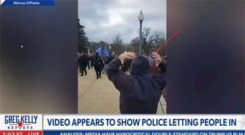 媒體錄象顯示,抗議人群被警察放行、進入國會大樓的入口區時,背對鏡頭的這個人揮舞雙臂為人群導流。(明慧網提供)