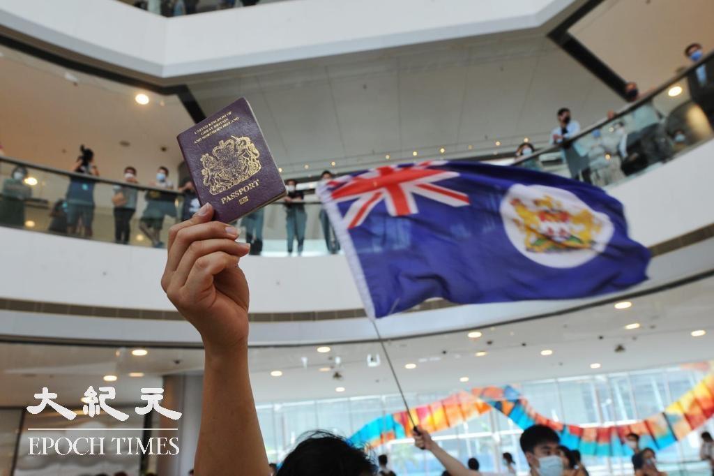 在2020年5月29日「中環和你lunch」的活動中,有市民舉起港英旗與BNO護照。(大紀元資料圖片)
