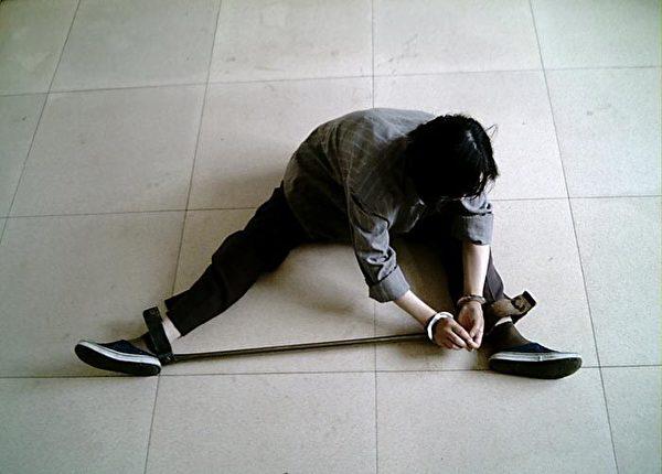 中共酷刑演示:戴鐵支棍。(明慧網)