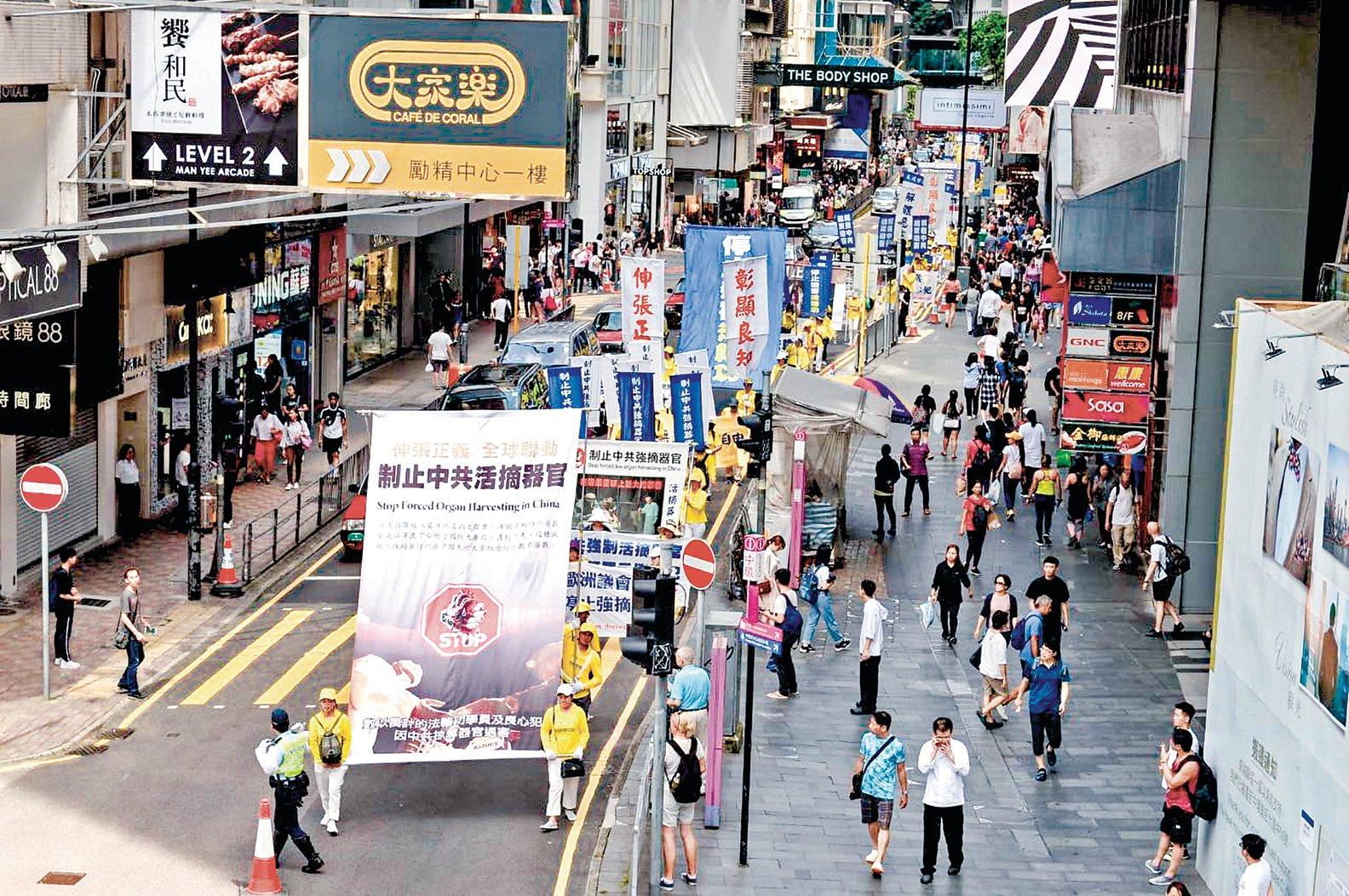 香港法輪功學員在反迫害游行中,打出「制止中共活摘法輪功學員器官」的橫幅。(大紀元)