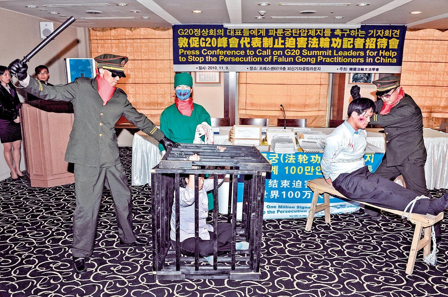 美國國會委員會報告顯示,目前中共仍然在繼續迫害法輪功。圖為韓國法輪功學員在漢城舉行的一個新聞發佈會上,向民眾演示中國警察如何對法輪功學員施以酷刑。(Getty Images)
