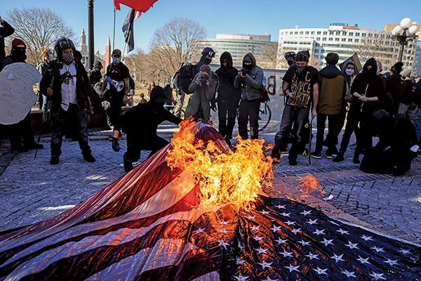 圖為2021年1月20日,在美國科羅拉多州丹佛市,美國共產黨和安提法組織成員在科羅拉多州議會大廈的台階上焚燒美國國旗。(Michael Ciaglo/Getty Images)