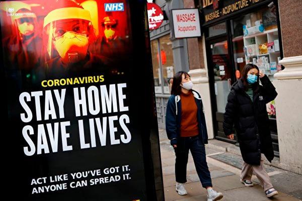 英國目前已出現了3種變種病毒,「致死率」比舊病毒更高。圖中為英國保健署(NHS)位於唐人街的居家防疫的宣傳牌。(TOLGA AKMEN/AFP )