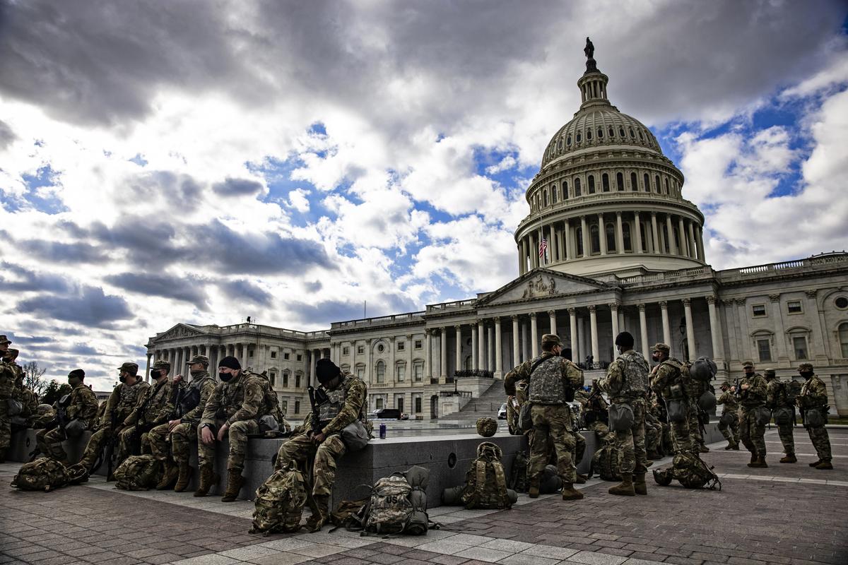 1月21日消息傳出,5,000名駐守華盛頓的國民警衛隊士兵受到粗暴對待,被趕進停車場。22日,前總統特朗普允許士兵住進他在DC的豪華酒店。已有三州州長令士兵撤回家園。約有200士兵確診中共病毒。圖為1月17日在美國會大廈東側的國民警衛隊士兵。(Samuel Corum/Getty Images)