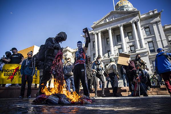 圖為1月20日美國共產黨及其它反法西斯團體成員在科羅拉多州丹佛市前府,焚燒美國國旗。(Michael Ciaglo/Getty Images)