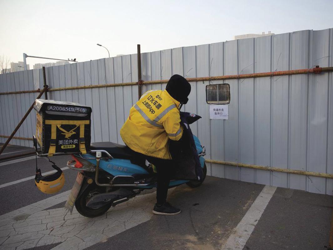 圖為快遞員向隔離區內遞快遞。(NOEL CELIS/AFP via Getty Images)