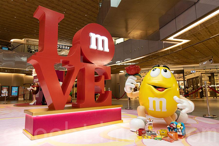 在「LOVE」雕塑裝置前跟阿黃拍照,甜甜蜜蜜有如「糖黐豆」。(陳仲明/大紀元)