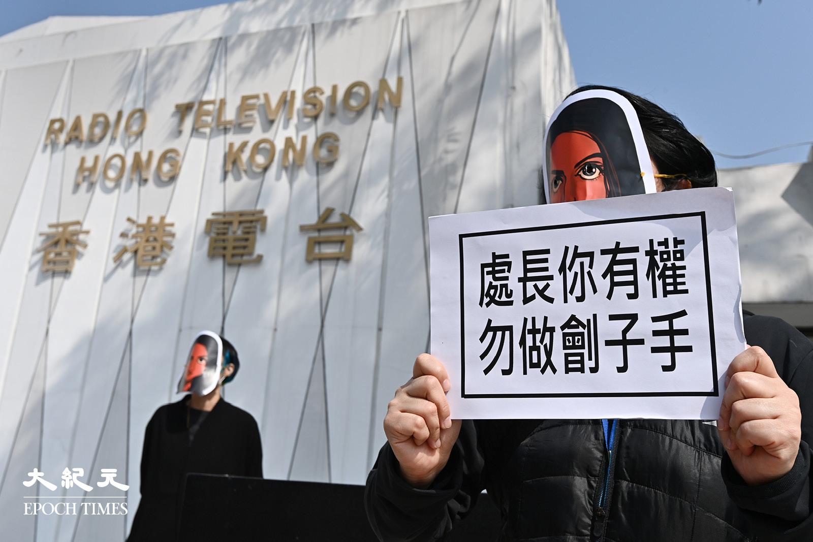 1月28日,香港電台員工戴上利君雅面具,手持標語聲援利君雅。(宋碧龍/大紀元)