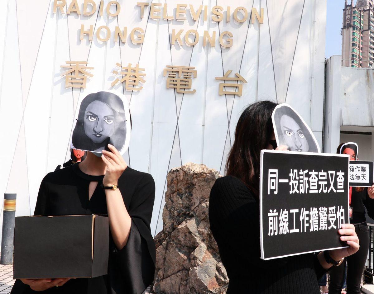 過百名港台員工戴上利君雅肖像面具快閃默站以表聲援,有人手持黑箱道具以諷刺管理層黑箱作業。(杜夫/大紀元)