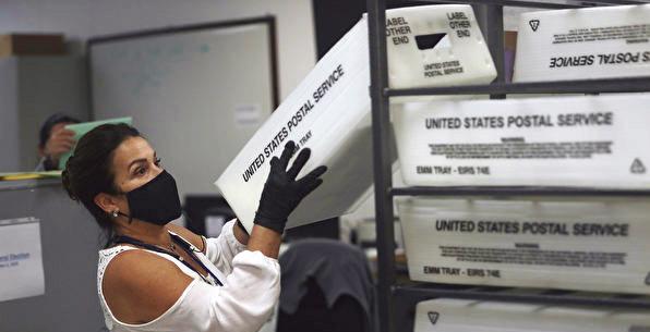 2020年11月3日大選日,邁阿密戴德縣選舉部門的一名工人正在統計郵寄過來的選票。(Getty Images)