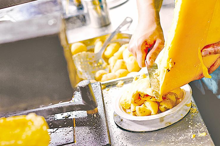 瑞士人用刀子刮下融化的芝士淋在熟薯仔上。
