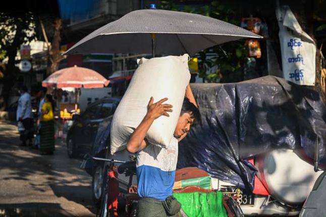 2月1日,由於緬甸進入緊急狀態,市民開始搶購物資。仰光一名男子搶購了一大袋米。(AFP via Getty Images)