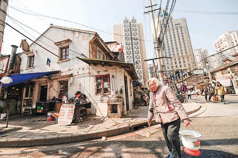 2013年3月,上海一名老人提著糞桶去公共廁所倒糞。(AFP)