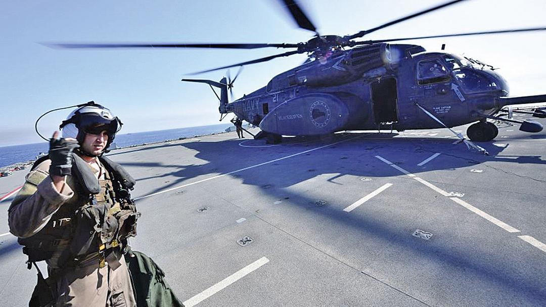 2019年4月15日,在美國、英國和法國海軍於阿拉伯灣舉行的聯合軍演中,一名參與演習的飛行人員正走向一架直升機。(Getty Images)