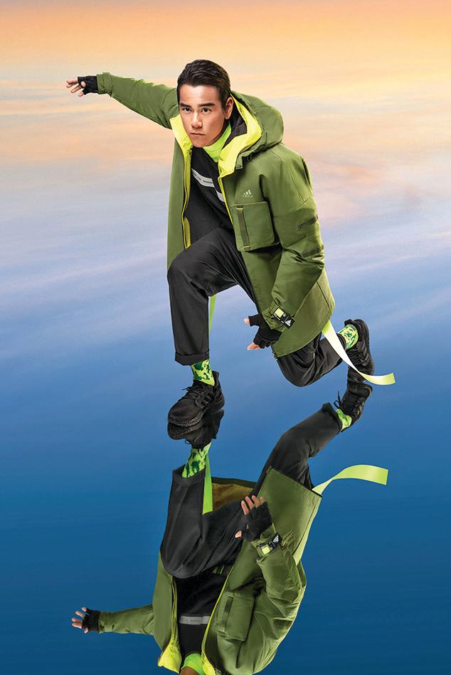彭于晏身著軍綠風衣外套,採用硬挺輪廓剪裁與鋪棉內層。
