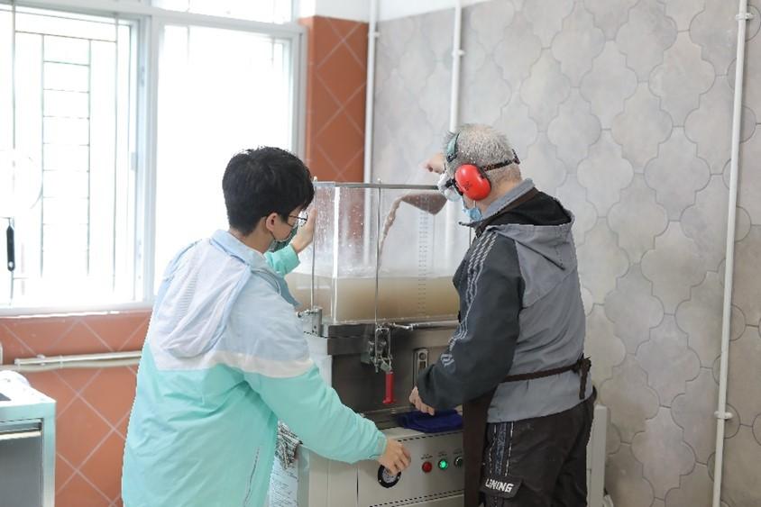 忻悅中心的會員在職員指導下利用抄紙機提升紙張成品的強韌度。(公關提供)