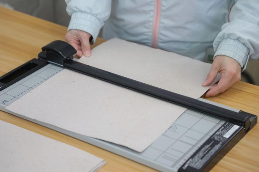 將再造紙切成嘉許狀所需的尺寸。(公關提供)