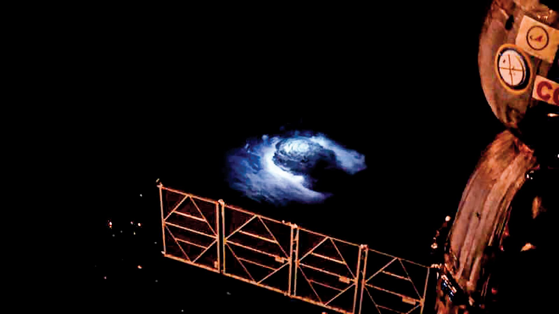 科學家第一次從國際太空站內俯視閃電的形成,看到了從厚厚的雲層內向上冒出一道藍光。(ESA/NASA)