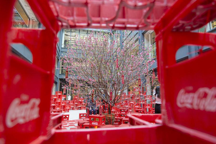 以逾500個「可口可樂」汽水膠箱及經典汽水玻璃樽拼砌而成吉祥如意扣形狀,市民可以遊走其中,尋找12呎高的桃花王。(南豐紗廠提供)