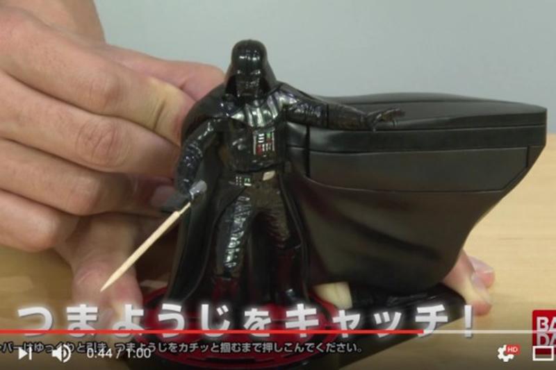 日本萬代株式會社推出黑武士造型的牙籤發放機,以牙籤取代光劍,頗具創意。(視頻擷圖)