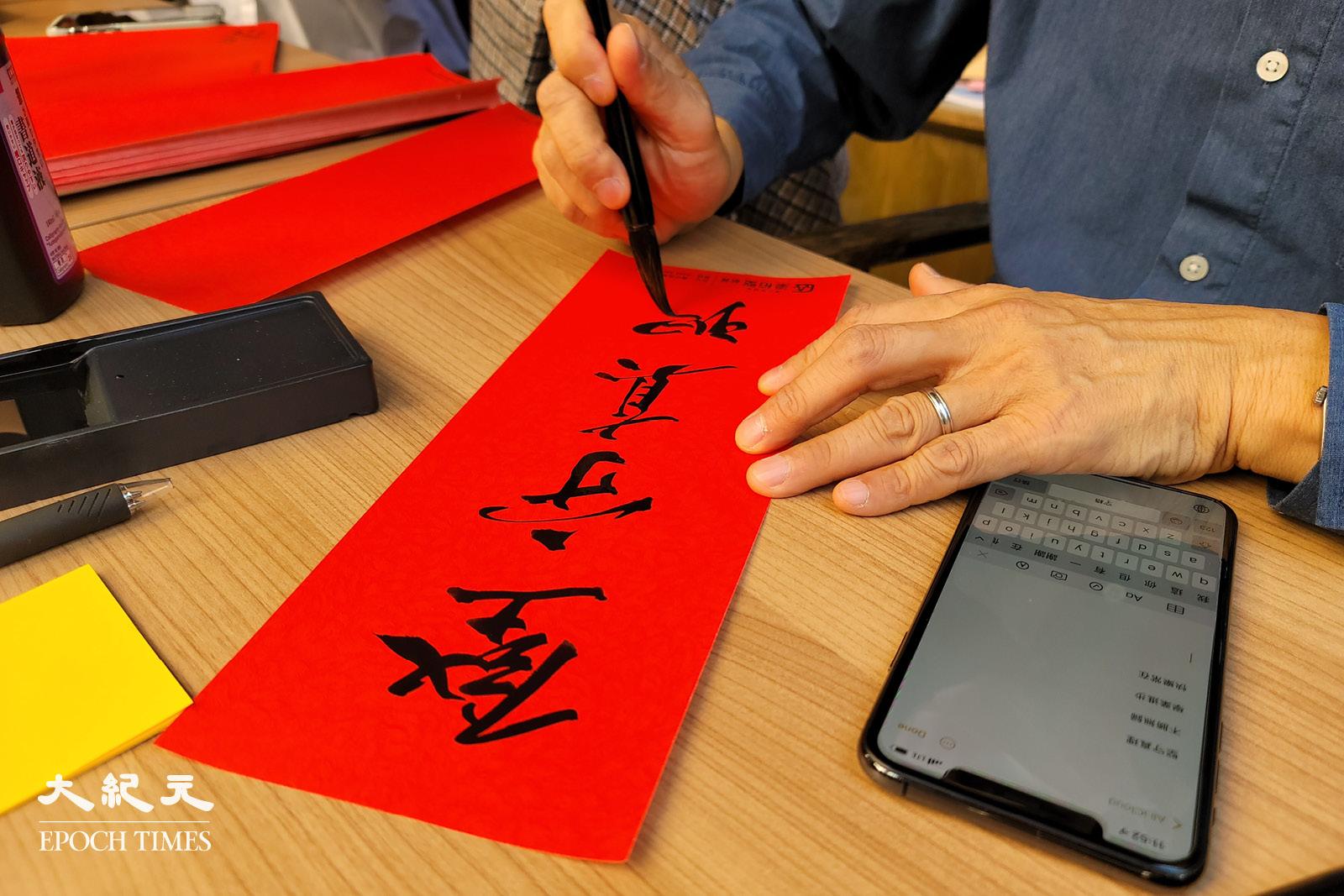 陳健民正在寫「堅守真理」。(宵龍/大紀元)