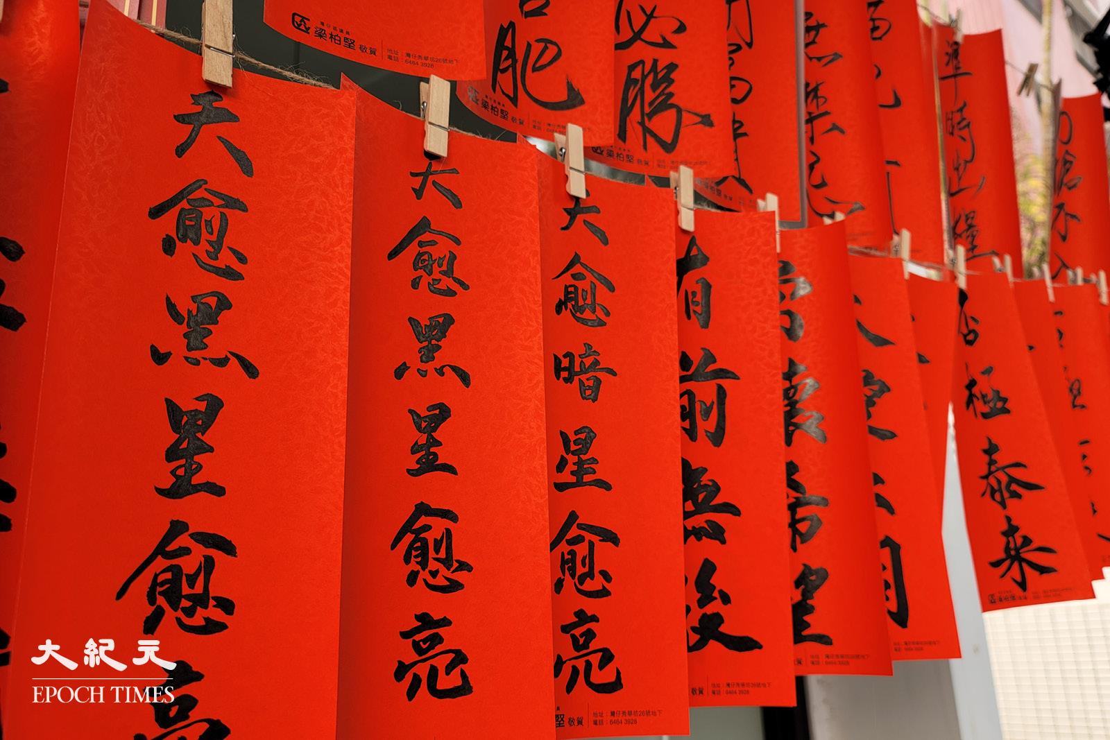 寫好的揮春掛起來等待領取,包括「天愈黑星愈亮」、「常懷希望」、「否極泰來」等字句,鼓勵香港人樂觀面對逆境。(宵龍/大紀元)