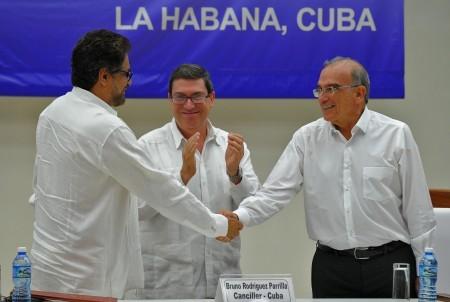 在結束談判後,哥倫比亞反對武裝的頭領馬爾克斯(左)與哥倫比亞政府代表德拉卡列(右)握手言和。(YAMIL LAGE/AFP/Getty Images)