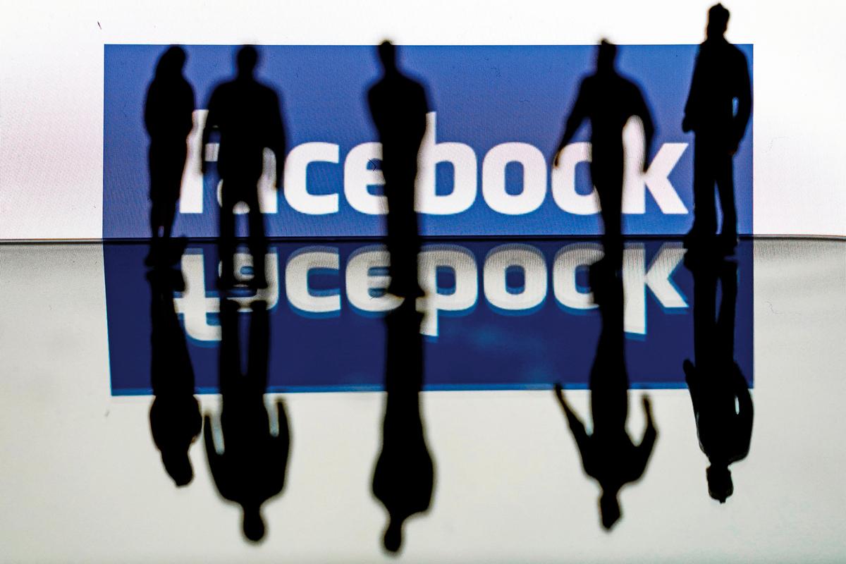 中共式的對社交媒體上言論自由的審查,正在美國發生。圖為幾個人站在臉書標誌前。(KENZO TRIBOUILLARD/AFP via Getty Images)