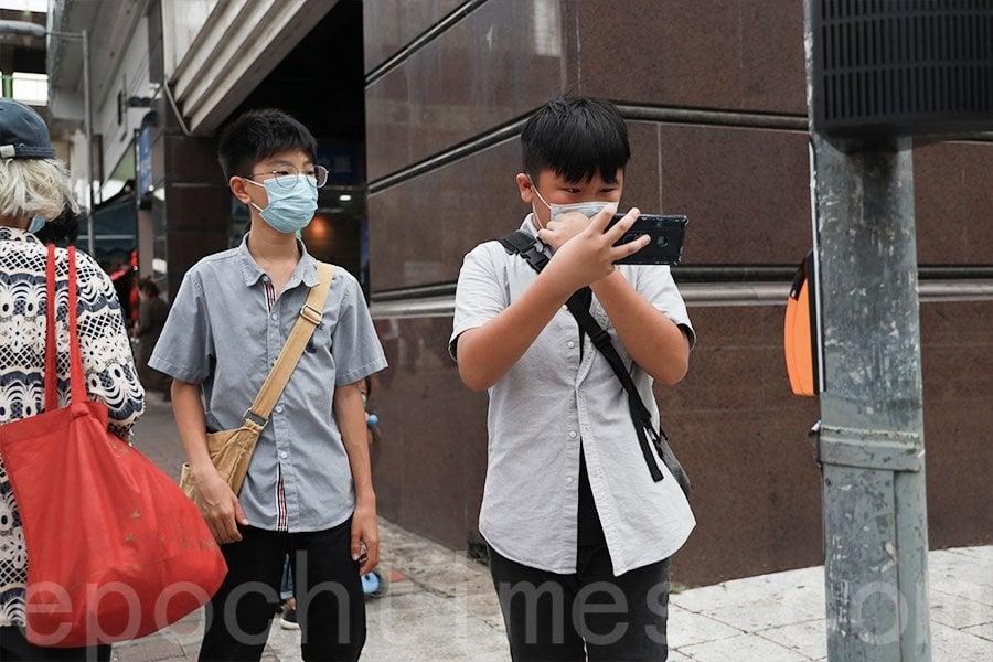 「天水圍社區關注組」主席兼創辦人,年僅11歲的王繼祖(右)經常關心區內事務。(陳仲明/大紀元)