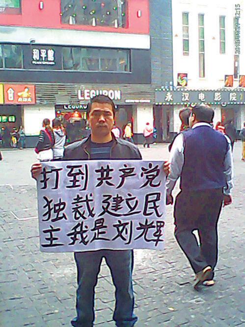 廣州「舉牌哥」劉輝在廣州繁華地段再次舉牌「打倒共產黨獨裁」。(網絡圖片)