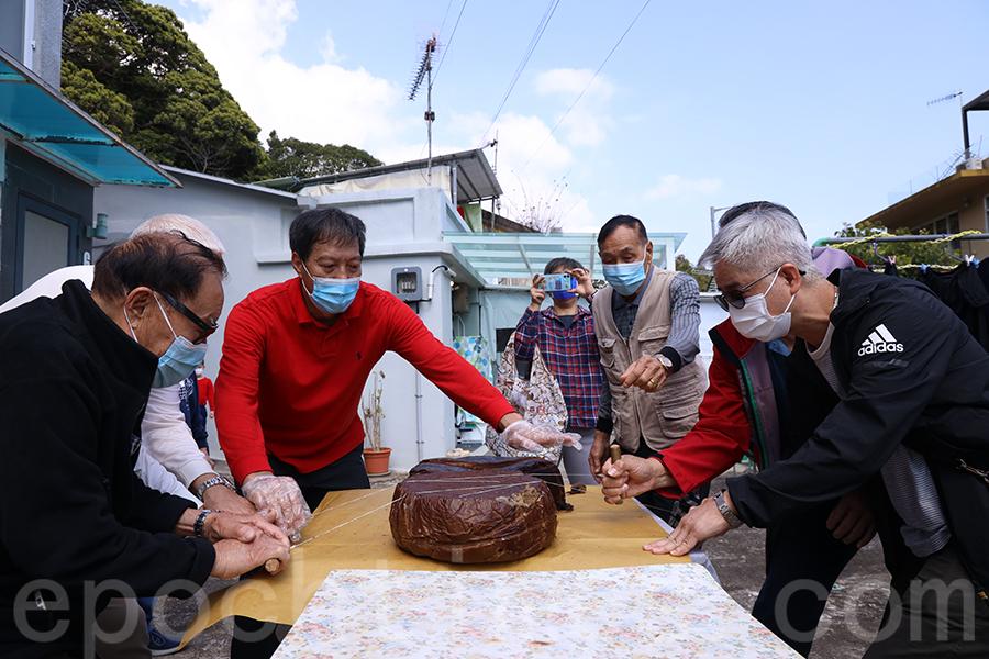 幾位步入耄耋之年的村民,在正月初三齊聚西貢上洋村劉氏家祠前,共同切開圓籠茶粿,分享童年的回憶。(陳仲明/大紀元)
