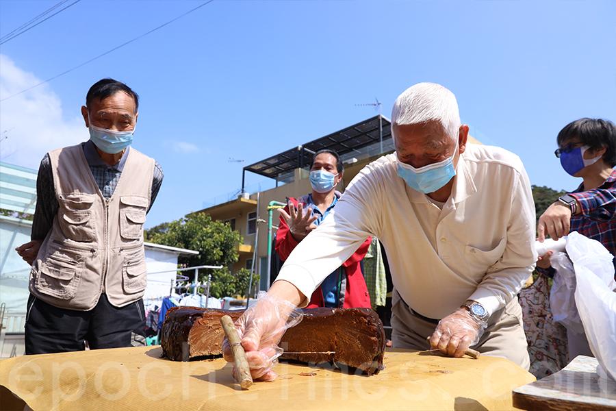 村民們齊心協力,把茶粿分割成一塊塊。(陳仲明/大紀元)
