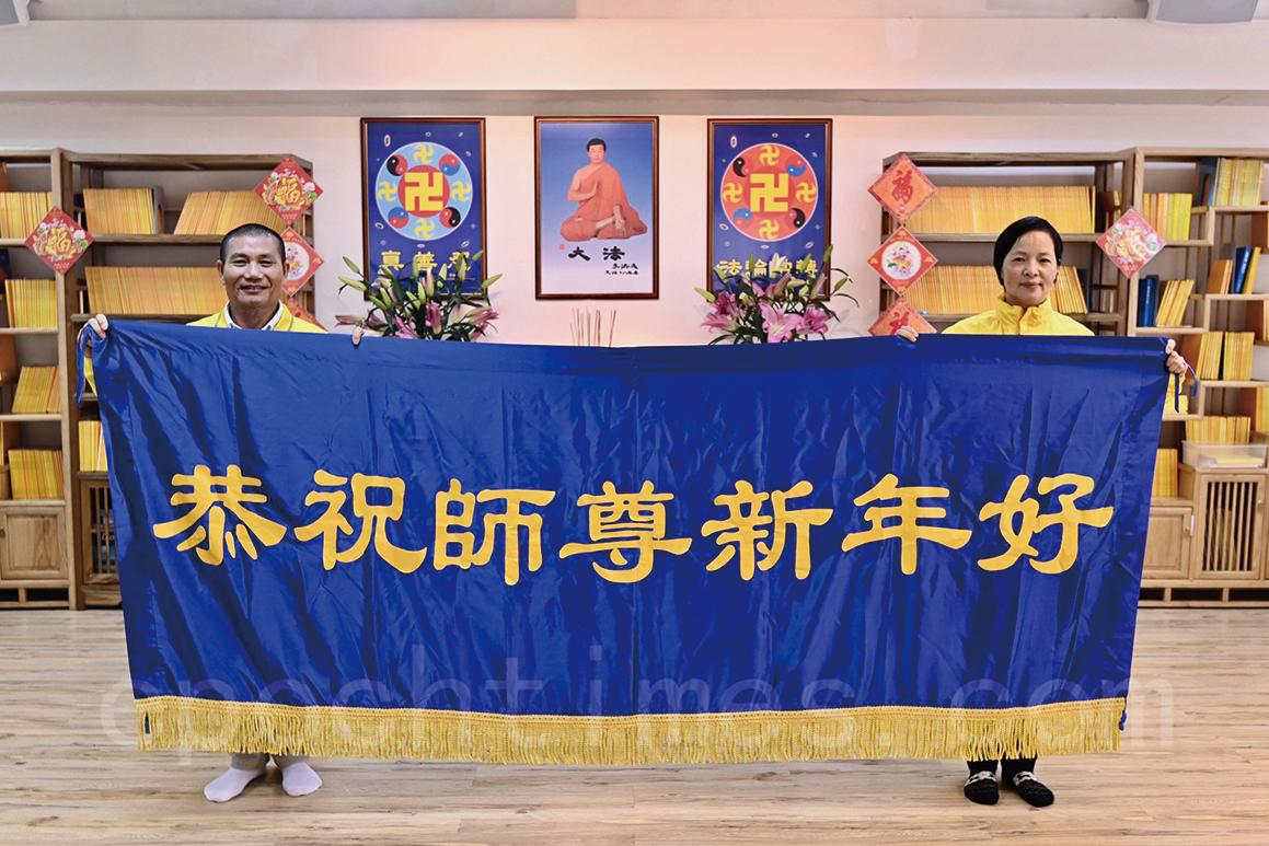 大年初一,香港法輪功學員洪先生(左)和陳小姐(右)向法輪功創始人李洪志先生拜年。(宋碧龍/大紀元)