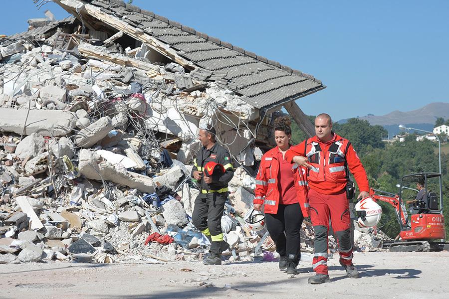 意大利中部24日發生黎克特制6.2級強震,導致多座古城小鎮嚴重受損。圖為重災區阿馬特里切鎮,在現場搜救的救難人員。 (ANDREAS SOLARO/AFP/Getty Images)