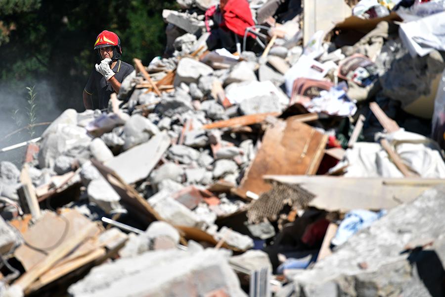 意大利中部24日發生黎克特制6.2級強震,導致多座古城小鎮嚴重受損。圖為重災區阿馬特里切鎮,救難人員在現場搜救。 (Photo by Carl Court/Getty Images)