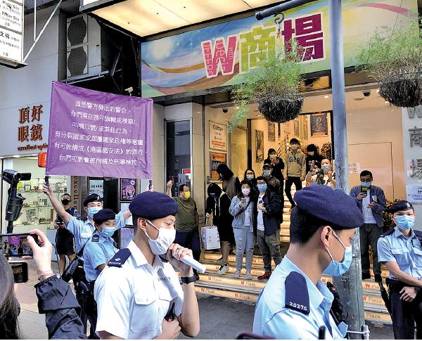 圍觀市民高呼「反送中」口號,警員舉紫旗警告違反「國安法」。(張曉慧/大紀元)
