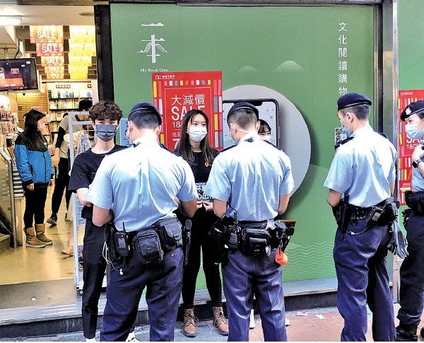 警員檢查旺角擺街站賢學思政學生的資料,警告違反限聚令。(張曉慧/大紀元)