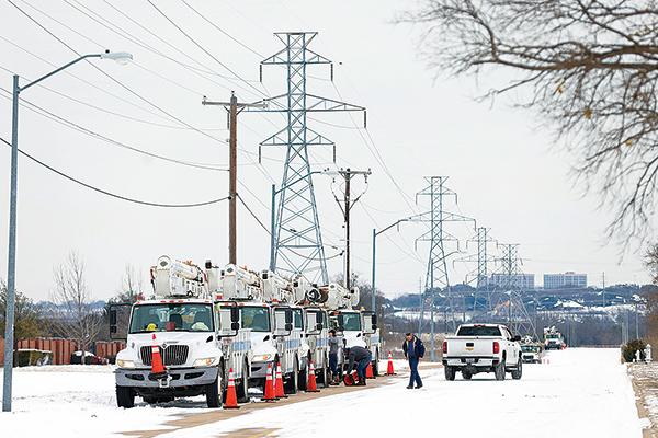美國德薩斯州經歷罕見冬季暴風雪,約310萬居民遭遇停電。圖為工程人員在修復電網。(Ron Jenkins/Getty Images)