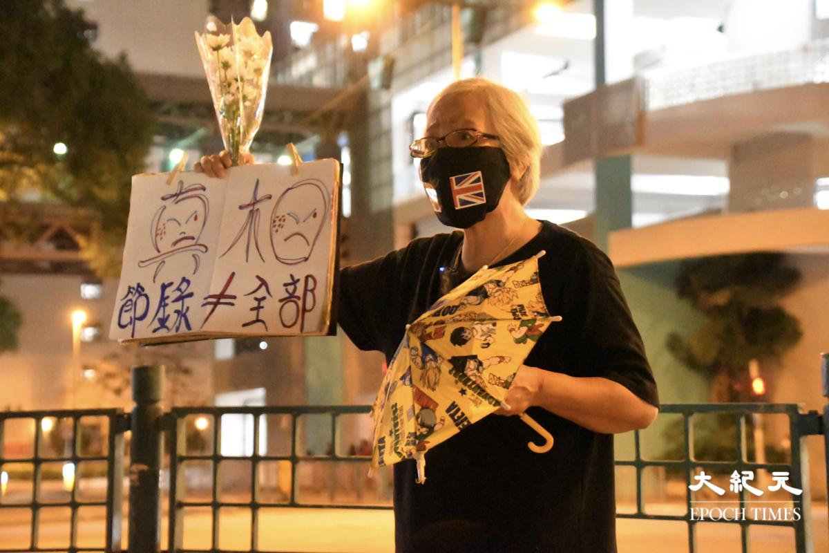 王婆婆手持白色鮮花及寫有真相、節錄不等於全部的紙牌,獨自在將軍澳紀念陳彥霖、周梓樂兩個在反送中運動中冤死的年輕人,被警方以公眾地方行為不檢拘捕。(Big Mack/大紀元)