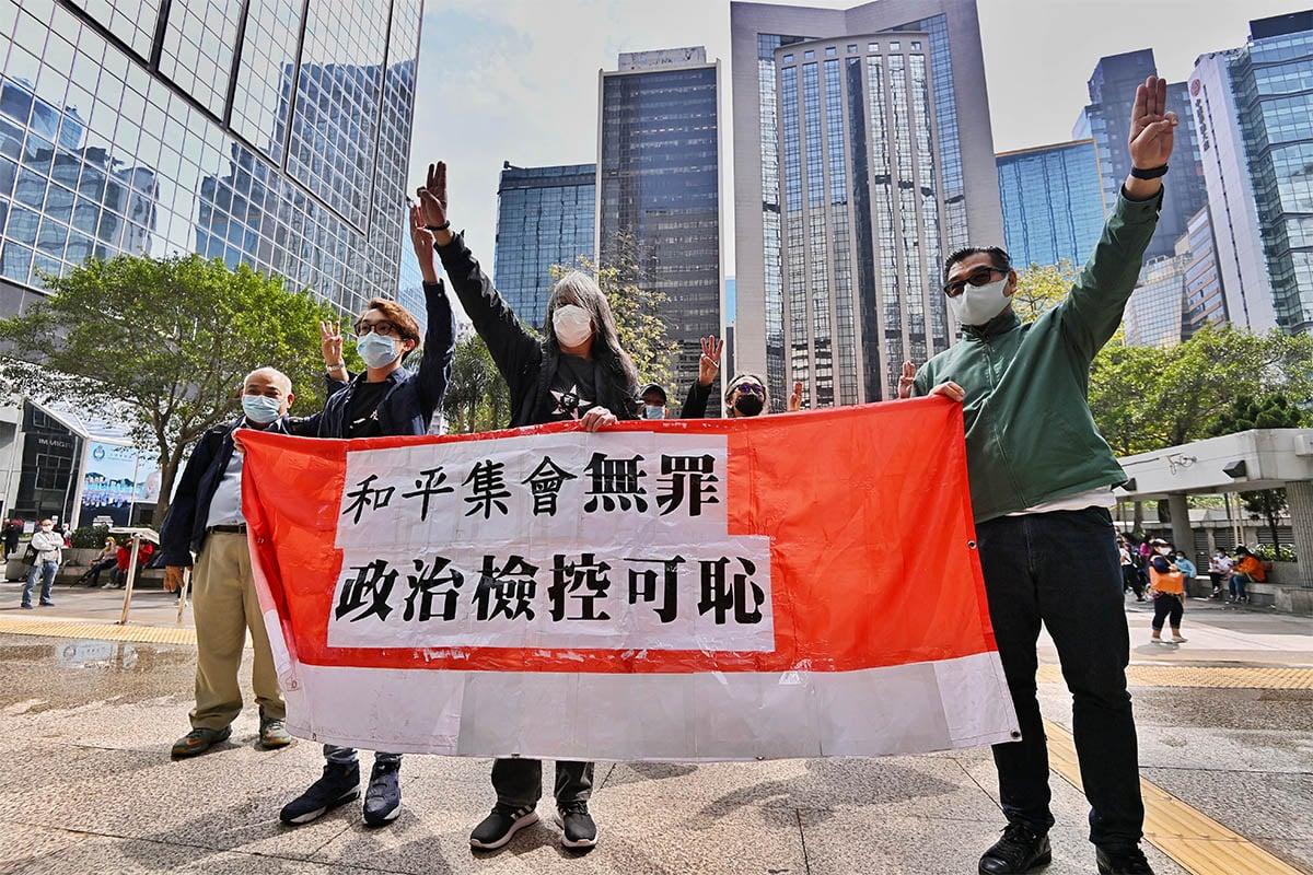 陳皓桓、梁國雄等人進入區域法院前手持「和平集會無罪,政治檢控可恥」橫額,並舉起3隻手指,聲援緬甸人反抗軍方政變。(宋碧龍/大紀元)