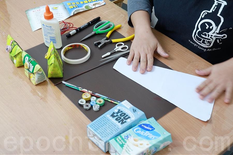 選一張單面廣告紙,將紙張對折成一個梯形,然後用一根竹籤在其中一角開始用力往上捲。(陳仲明/大紀元)