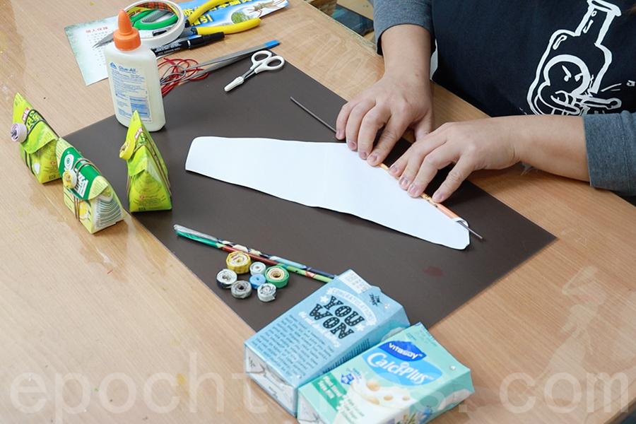將竹籤放在紙條的一端,手指壓著由內往外捲。(陳仲明/大紀元)