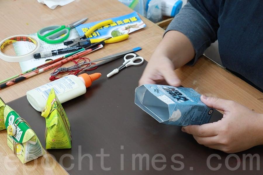用剪刀沿著頂線剪開回收的飲品紙盒,將盒子洗乾淨吹乾備用。 (陳仲明/大紀元)