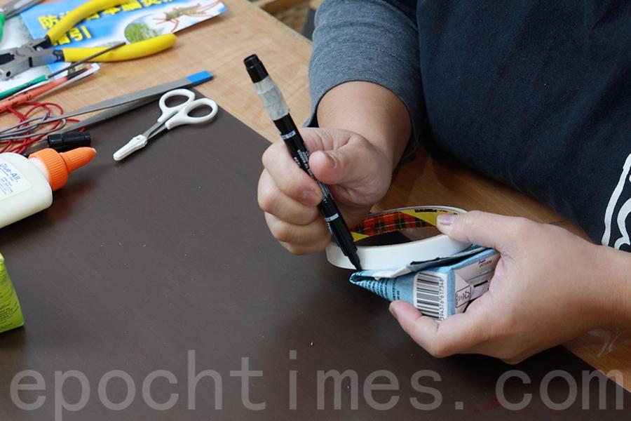 在紙盒吸管下處放上圓規或雙面膠卷,畫一個半圓形。(陳仲明/大紀元)