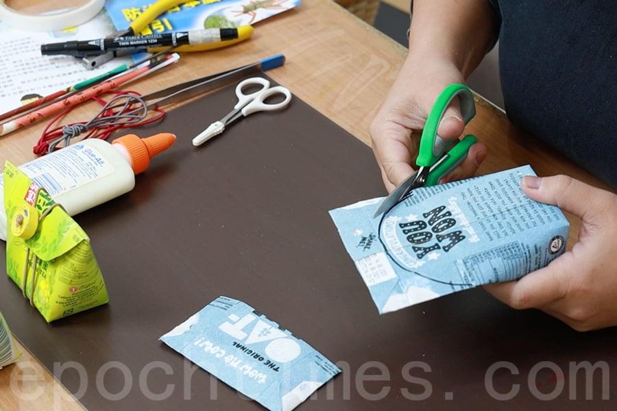 用剪刀剪掉沒有半圓形標記的一面,接著用剪刀沿著半圓形進行裁剪。(陳仲明/大紀元)