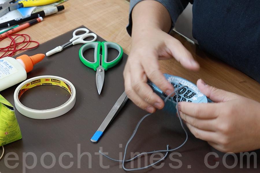 將橡皮筋從內側穿出洞口外側,然後拉緊橡皮筋將其對齊。(陳仲明/大紀元)