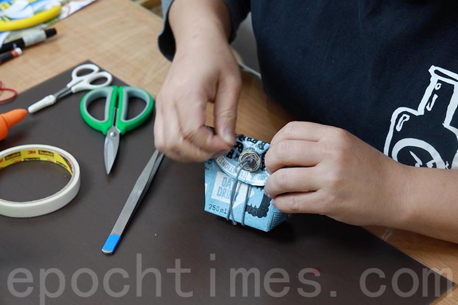 橡皮筋穿入早前準備好的紙鈕之中,紙鈕緊貼紙蓋。(陳仲明/大紀元)