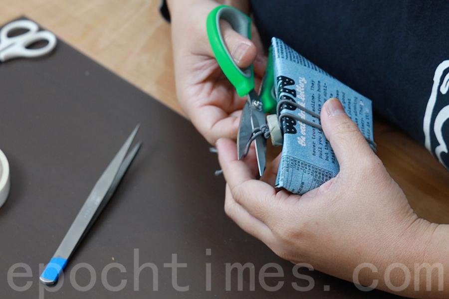 觀察橡皮筋穿過鈕扣後的鬆緊度,如果過鬆可以拉動末端調整。調整完後,在靠近鈕扣尾端打結。(陳仲明/大紀元)